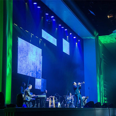 Modern Warrior performance on stage with multimedia screens at Natcon