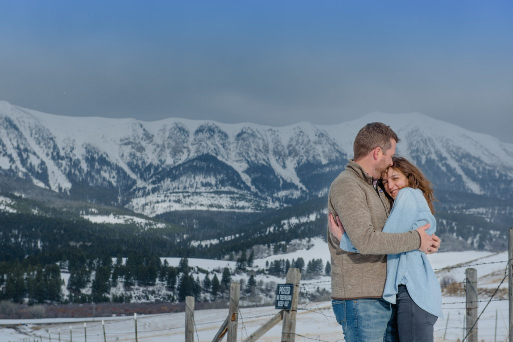 couple embracing in front of snow capped mountains