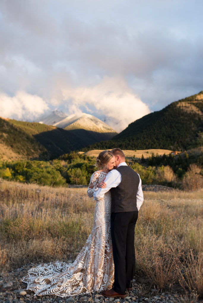 Wedding photo of bride and groom with mountain backdrop