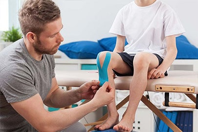 A physical therapist caring for a young patient's knee injury.