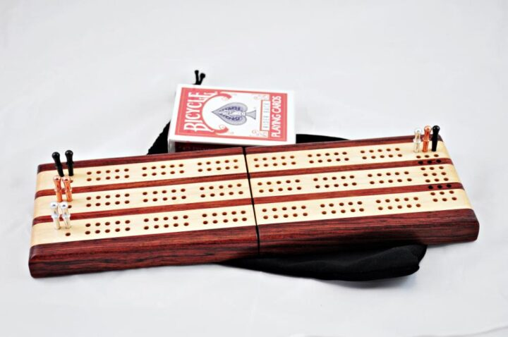 Bubinga and Maple 3 Player Travel Cribbage Board. laying flat and ready for play!