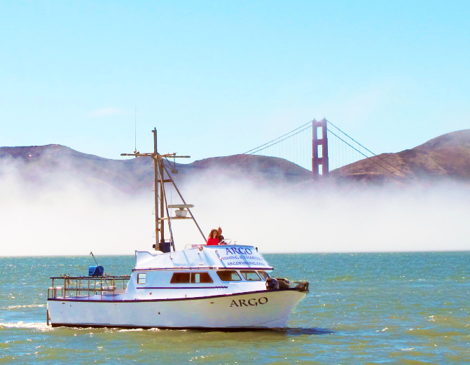 Fishing boat Argo in front of Golden Gate Bridge with white fog in background