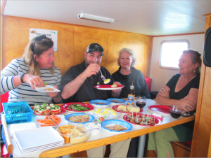 people enjoying a range of food and drink at table inside boat