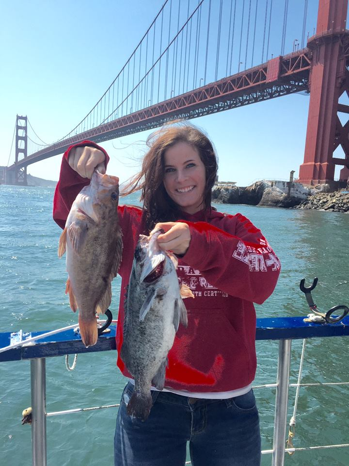 Woman in red sweatshirt holds two rockfish on the back of the fishing boat Argo with the Golden Gate Bridge right behind her