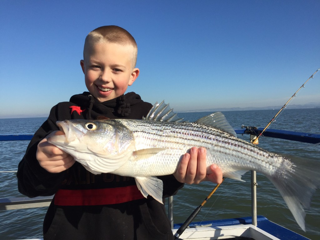 Smiling little boy holding a striped bass horizontally