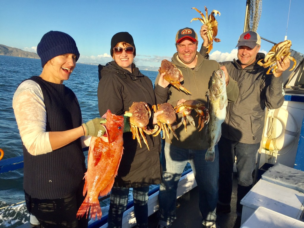 A group of two women and two men hold up several fish and crabs on Argo boat