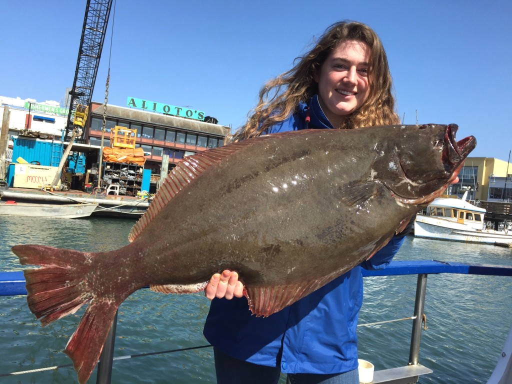 Young woman holding a large halibut on a boat