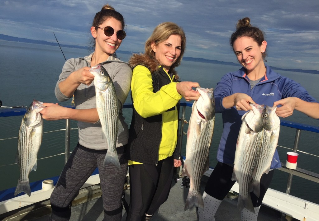 Three smiling women hold striped bass on a boat