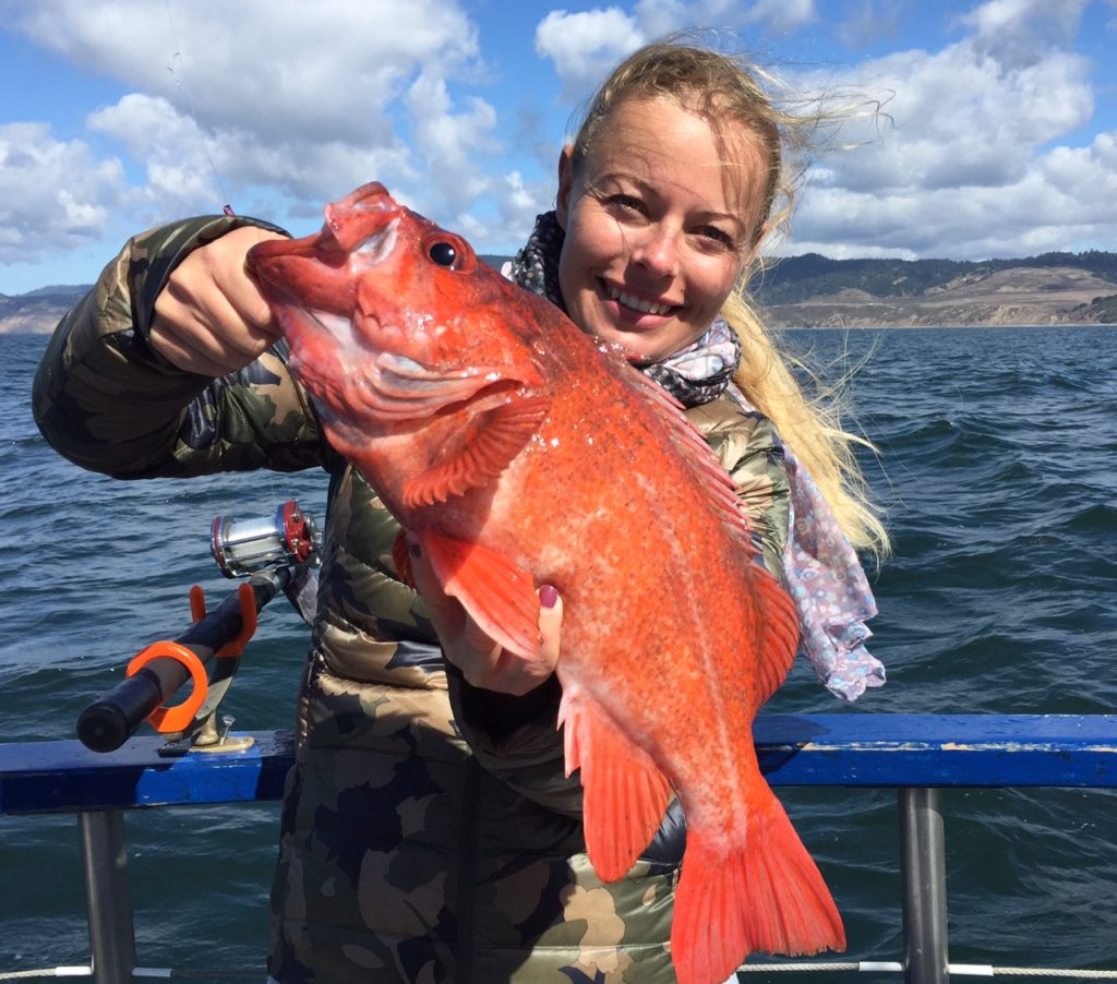 woman holding a large red vermillion fish on a boat