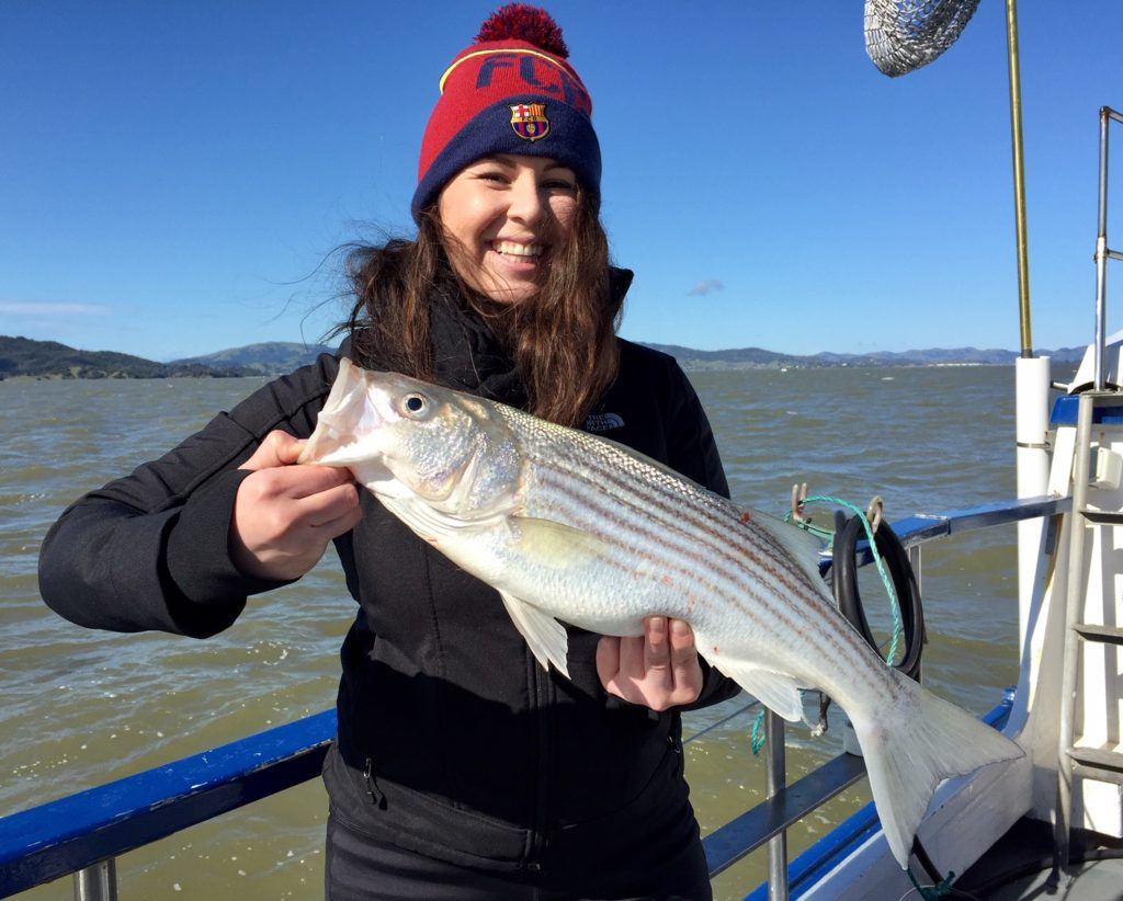 Smiling woman in a winter hat holds a striped bass on a boat