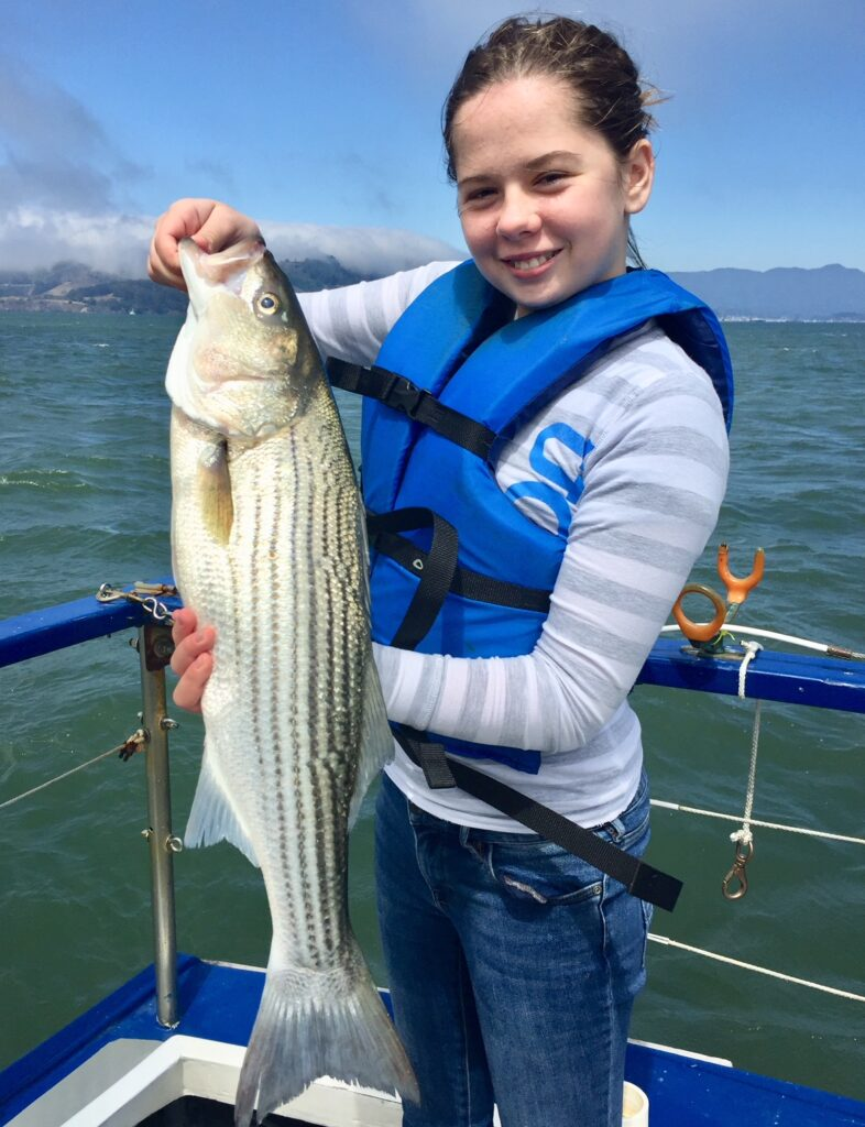 Girl holds striped bass on boat