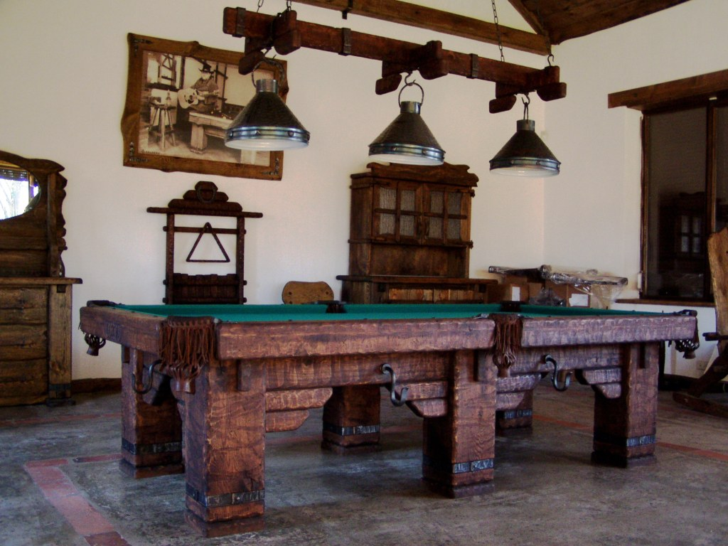 Wild West rustic log hand-made pool table by Vision Billiards showroom