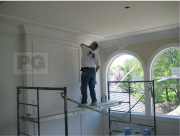 painter repairing wood trim and drywall before painting