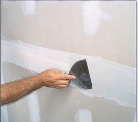 painter applying drywall compound to wall before painting