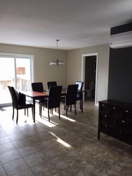 shows a living room dining room painted with Kendall Charcoal focal wall, other walls painters used Revere Pewter all benjamin moore paints