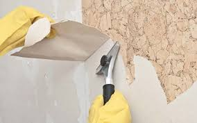 painters hand removing wallpaper from wall before painting
