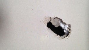 hole in a white painted wall