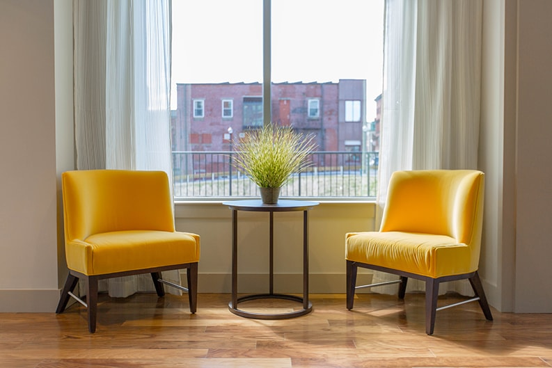 interior painted living room by painting company with two yellow side chairs in front of window with curtains