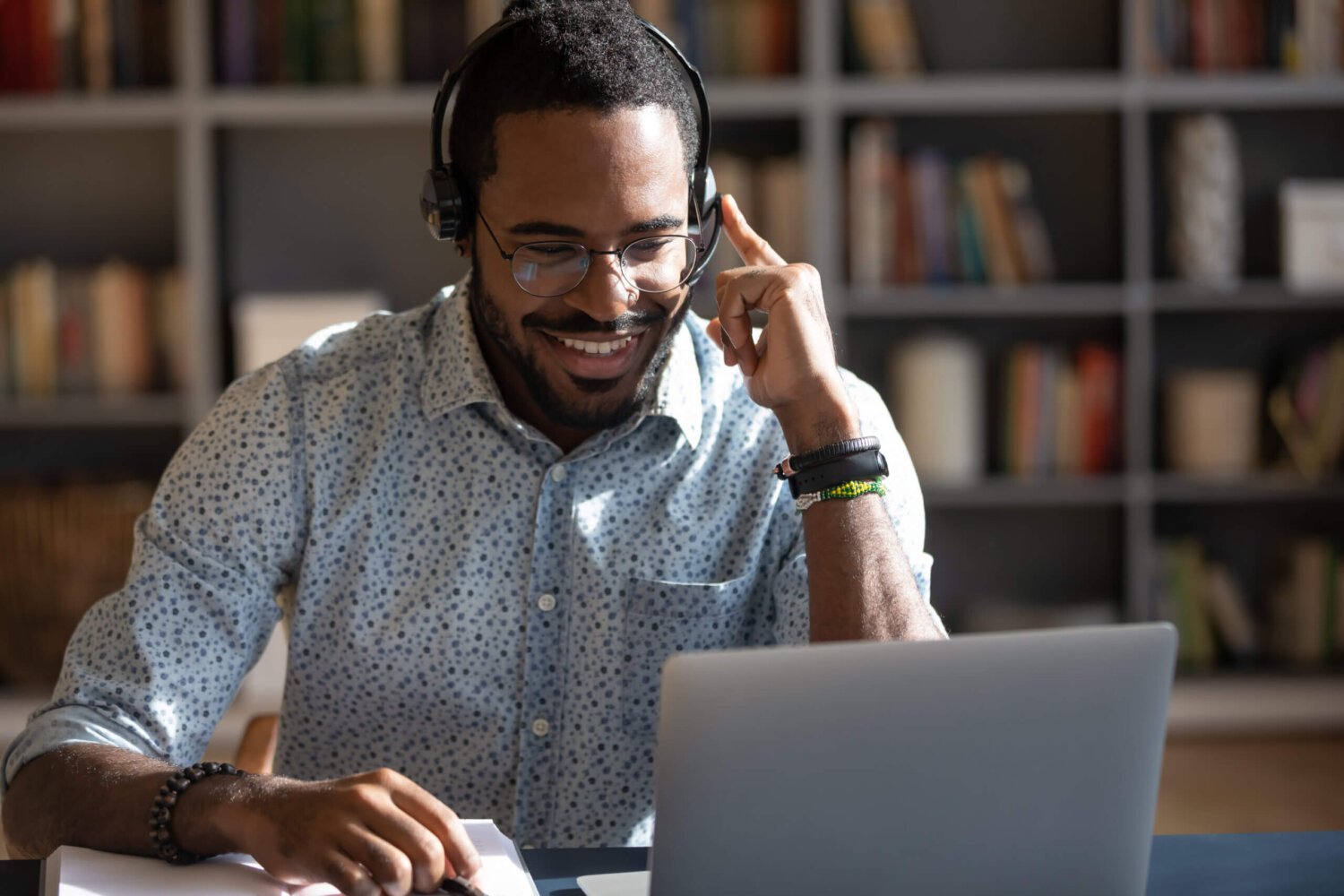 Insurance agent guide to insurance enrollment period in 2020 Focused African man sitting at desk wear headset watching webinar video course gain new knowledge use on-line application website. Manager talk to client provide professional help and support concept