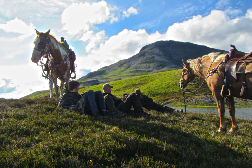 Horses on top of a mountain and riders relaxing