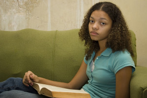 Bored Teenager Girl With Book In Poverty Style Home