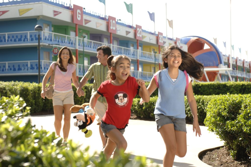 Two girls running and having fun in front of one of the buildings at Disney's All-Star Sports resort