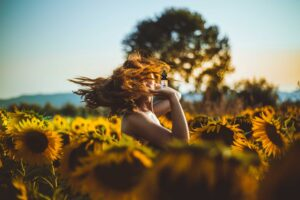 woman in sunflower field holding cbd oil of dayton bottle