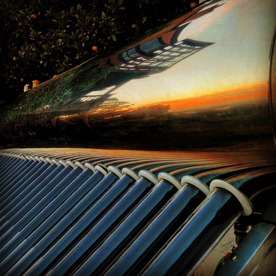 Beautiful artistic shot of an evacuated tube solar water heater with tank Sunbank 80G at sunset