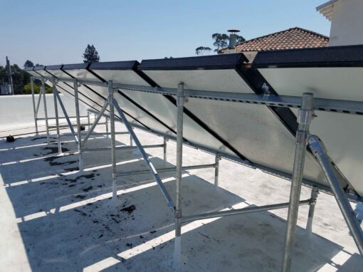 Photo of an array of flat plate solar water heater collectors, taken from the back, mounted on Hollaender Speed Rail on a flat roof of a multifamily commercial building