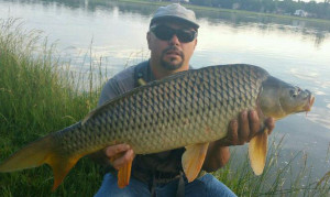 Mike Medina proudly holds a 21 pound common carp along the shores of a tranquil lake.