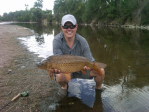 Carp held by happy angler with fly rod laying beside him