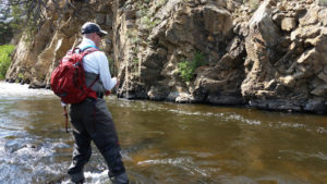Man wearing red backpack wading in stream with bent fly rod and a rocky backdrop.