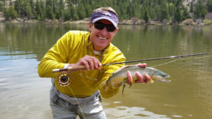 Fly fishing angler holds a brown trout with one hand and fly rod with the other