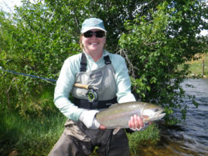 Woman poses with Colorado rainbow trout with fly rod tucked away under her arm