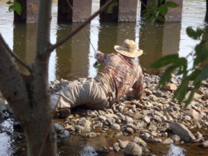 Fly fishing guide Chris Galvin lays on his side on the rocky edge of a river extending his fly rod to present to wary carp