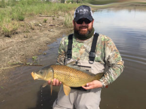 All smiles as this fly fisherman holds a healthy common carp.