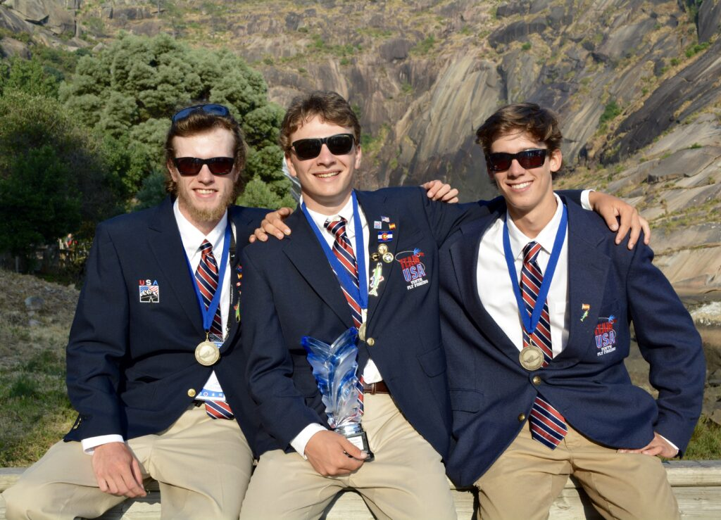 Well-dressed U.S. Youth Fly Fishing Team members embrace with medals around necks.
