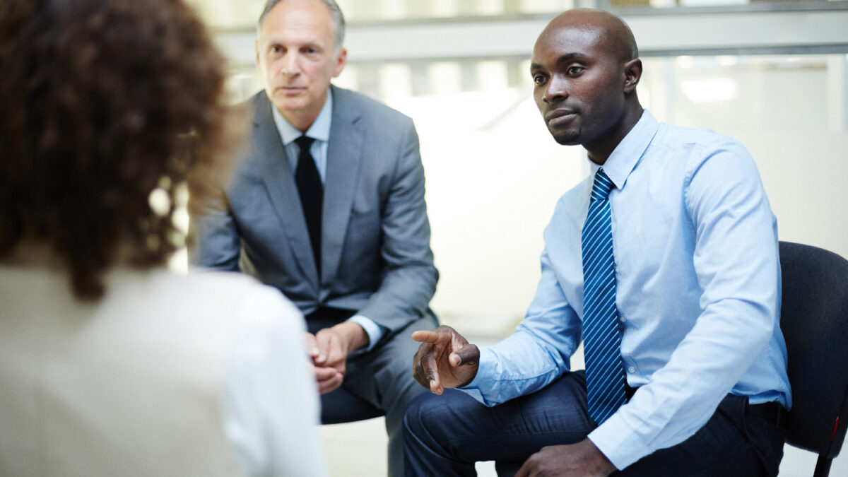 Attentive men listening to their female colleague during discussion at business training
