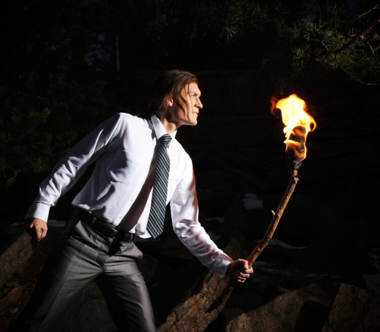 man with burning stick while moving in darkness