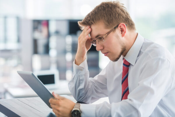 Business man with tablet thinking in an office