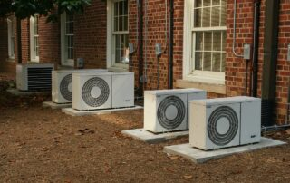 Commercial AC units sitting outside a multi-home building.