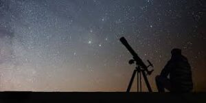 Siloette of a small refracting telescope against a starry sky