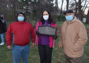 Two men and one woman stading outside, wearing masks. Woman in center is holding a palacque