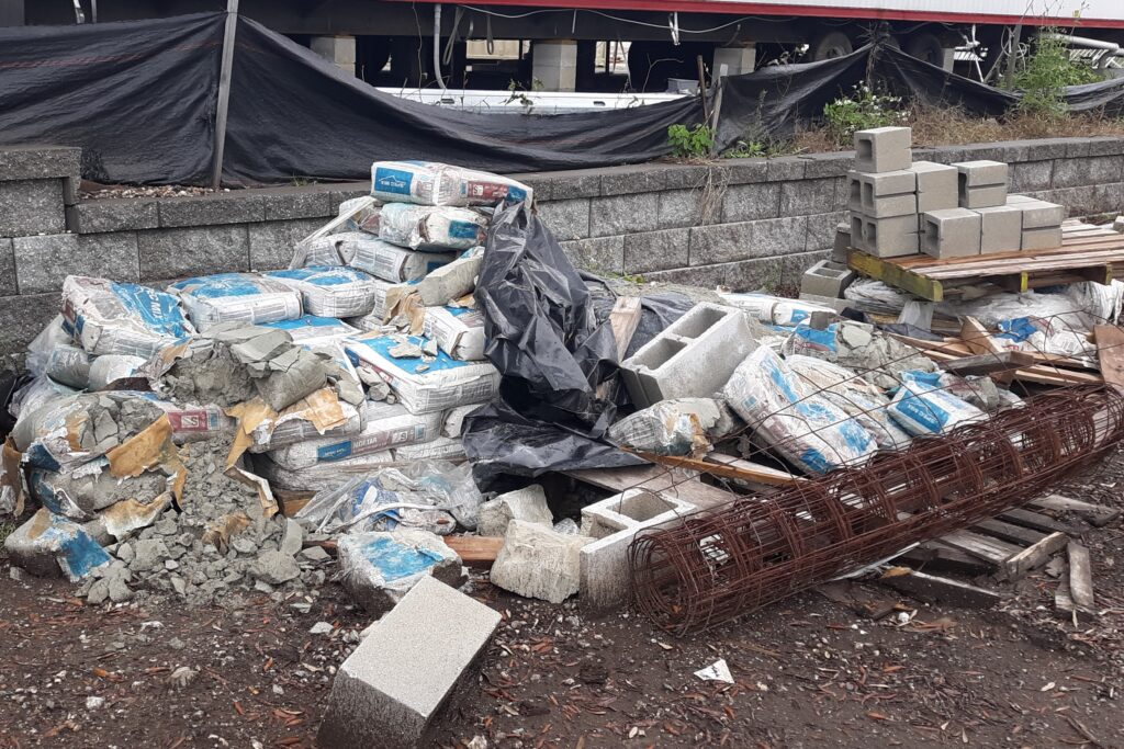 Material Stroage area below office trailer PIle of exposed to weather mason mix bags and debris to be removed