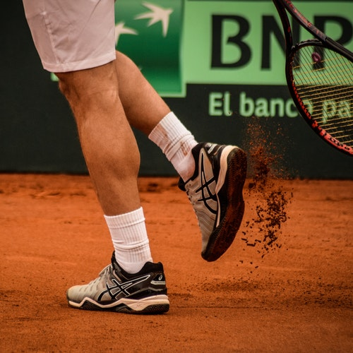 man-wearing-black-and-white-asics-athletic-shoes-holding-1432034