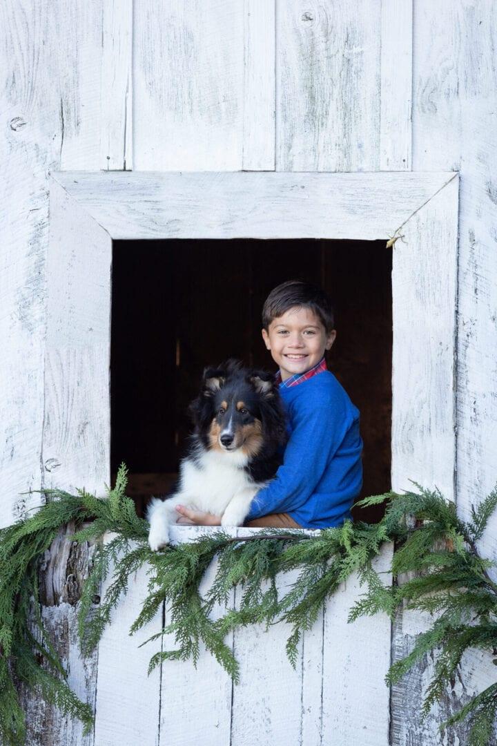 Boy in festive barn window with dog