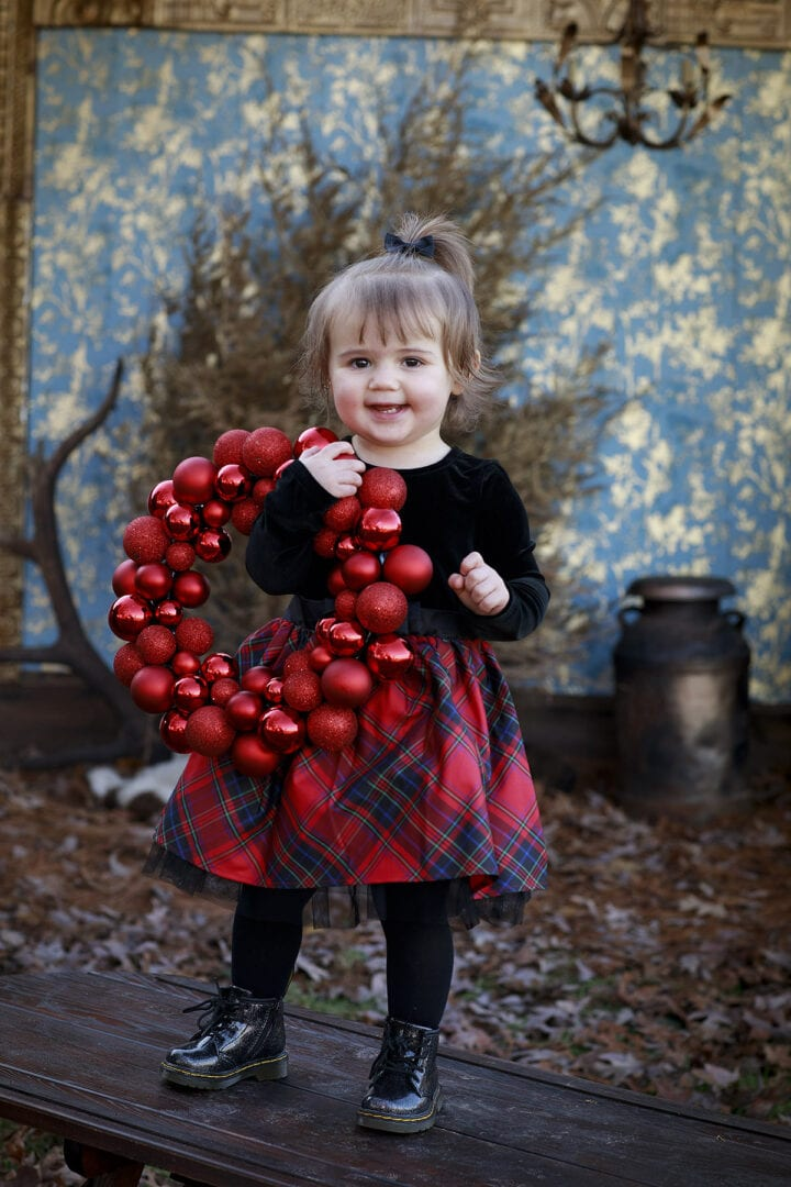 little girl with red ball wreath