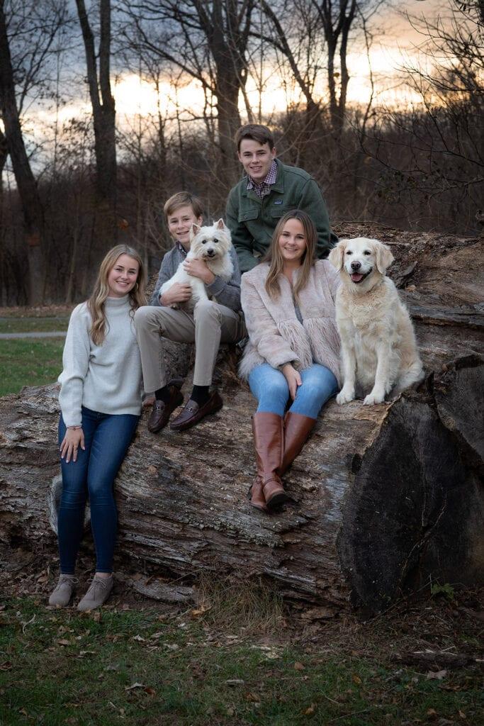 Family photo with dog on large wood pile