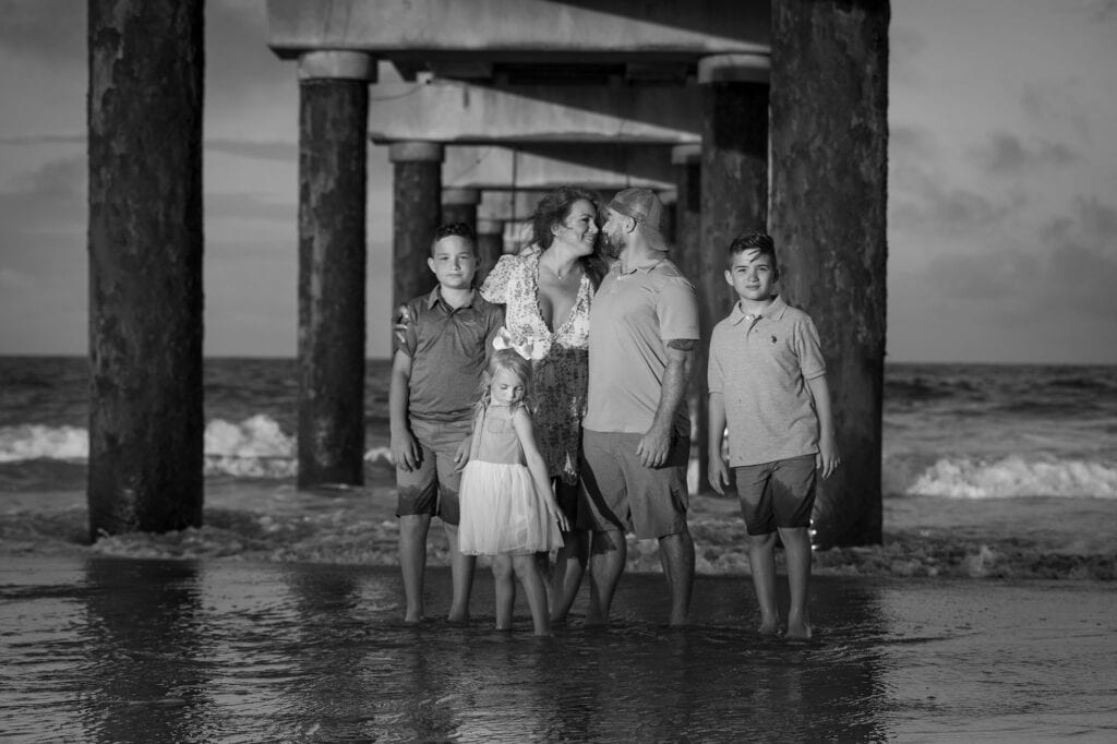 Family under a pier on the beach at sunset
