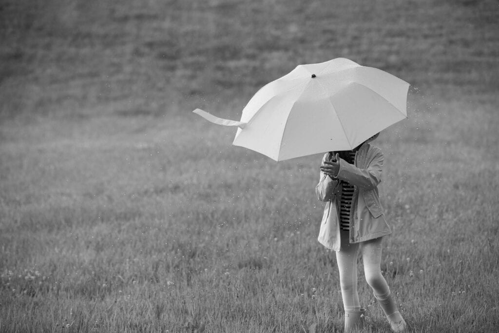Girl in field with umbrella in a rain shower, Middleburg Virginia